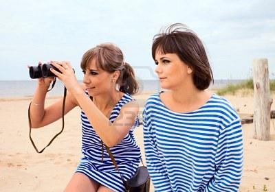 9799128-girls-looking-through-binoculars-on-a-beach.jpg